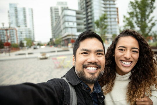 POV Portrait happy couple taking selfie in city