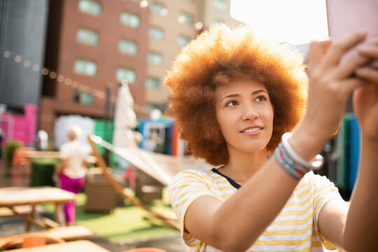 Young woman with smart phone taking selfie at urban bazaar marketplace