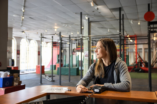 Woman with credit card paying for gym membership at front desk
