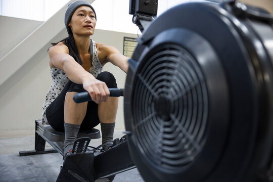 Athletic woman using rowing machine in gym
