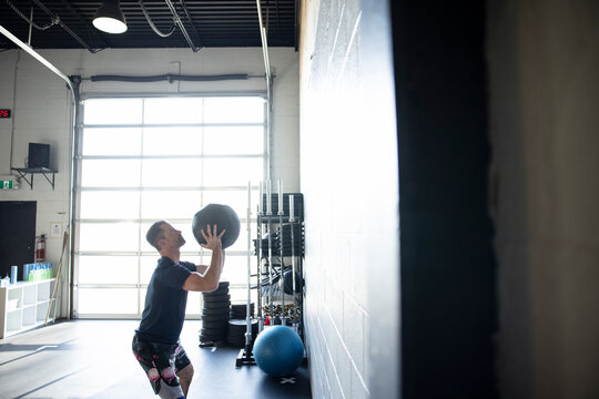 Man doing medicine ball throws at all in cross training gym