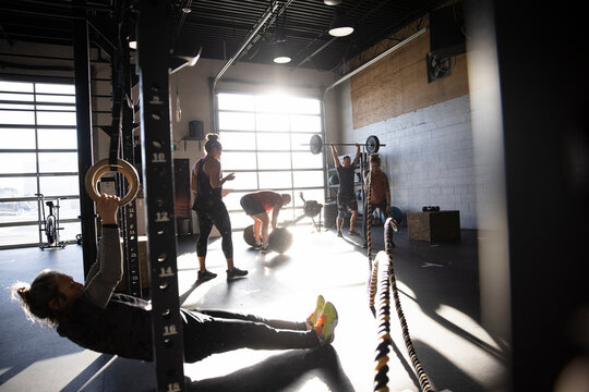 People working out with equipment in sunny cross training gym