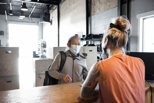 Gym member in face mask talking with owner at front desk