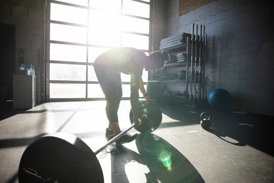 Man preparing barbell in sunny cross training gym
