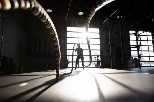 Silhouette woman using battle ropes in sunny cross training gym