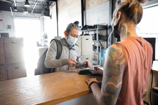 Man in face mask paying for gym membership at front desk