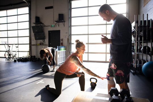 Personal trainer guiding client in cross training gym