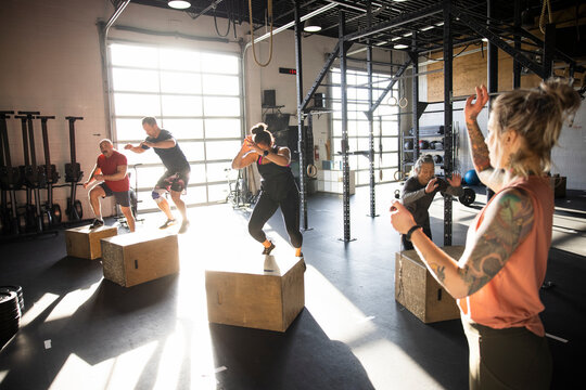 Cross training group class doing box jumps in sunny gym