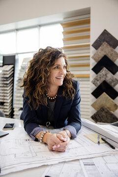 Portrait of interior designer with blueprints in showroom office