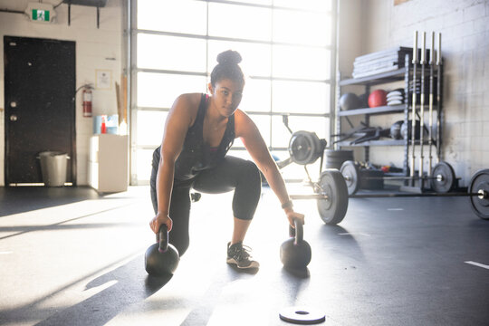 Portrait confident young woman working out with kettlebells in gym