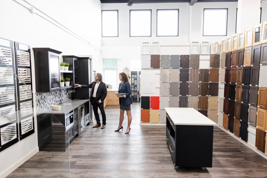 Saleswoman and customer looking at cabinets in kitchen showroom