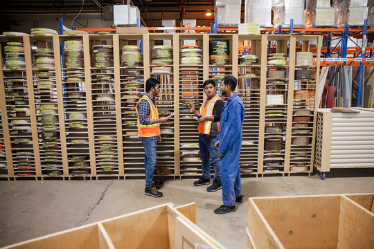 Mentor and workers discussing work in distribution warehouse