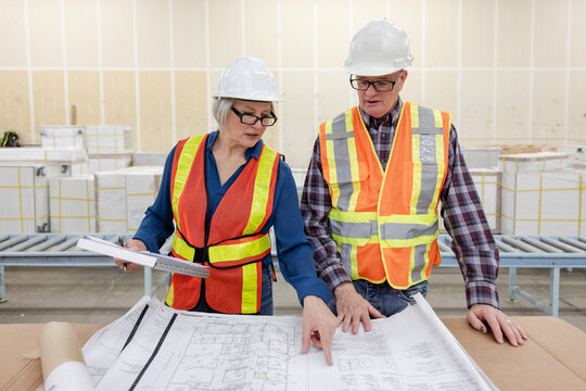 Architects working on blueprint in distribution warehouse