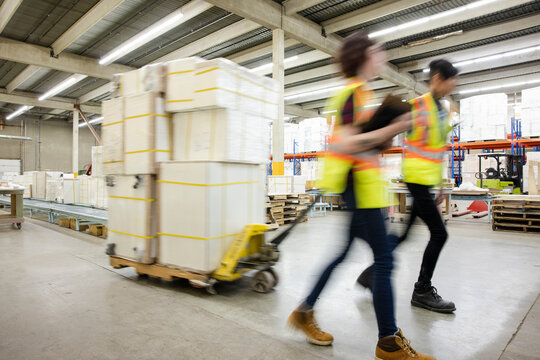 Workers moving cargoes in distribution warehouse
