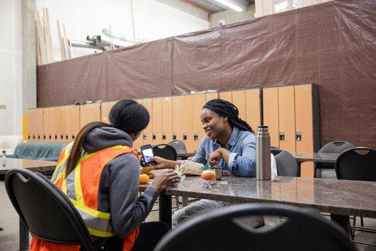 Colleagues using phone at breaktime in locker room