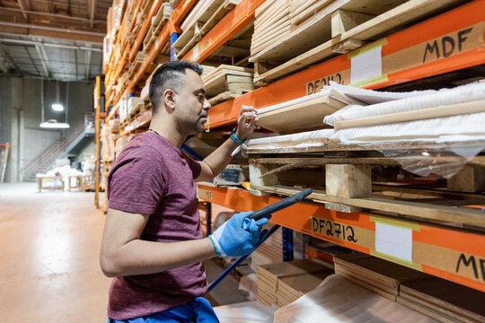 Worker checking building materials in distribution warehouse