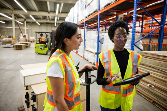Colleagues working with digital tablet in distribution warehouse