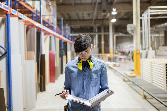 Worker writing notes in distribution warehouse