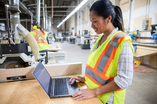 Worker working with laptop in distribution warehouse