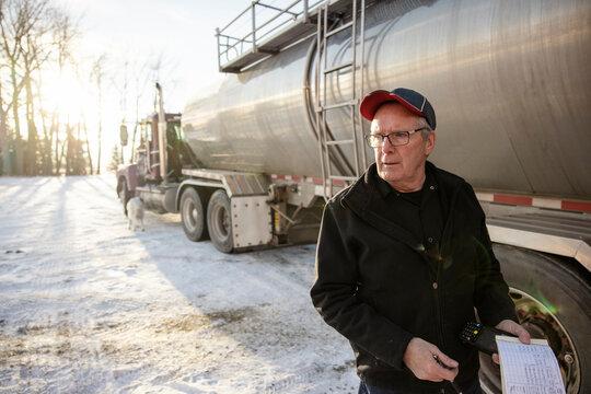 Portrait of driver beside milk tanker truck
