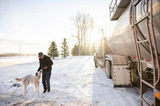 Driver patting dog beside milk tanker truck