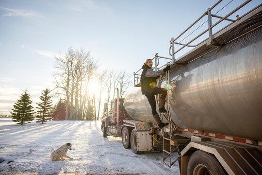 Female farmer climbing steps of milk tanker truck