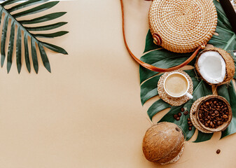 Summer background with Ratan bag, leaves monstera, coffee cup and coconut on brown background. Flat lay, top view