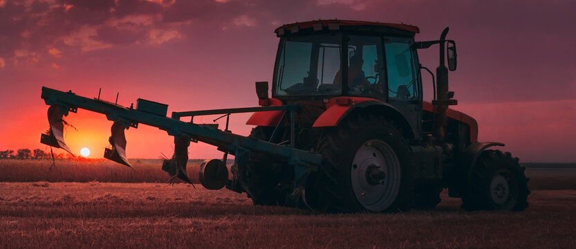 Tractor with a raised plow in an agricultural field against the backdrop of a sunset. Plowing after harvest. Concept, agriculture, food industry. Selective focus, toned photograph.