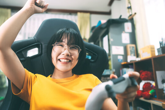 Young adult asian gamer woman wear eyeglasses play a online game.
