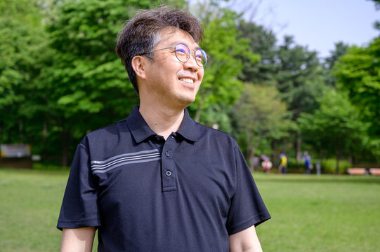 Portrait of a middle-aged Asian man smiling on the lawn wearing a T-shirt.