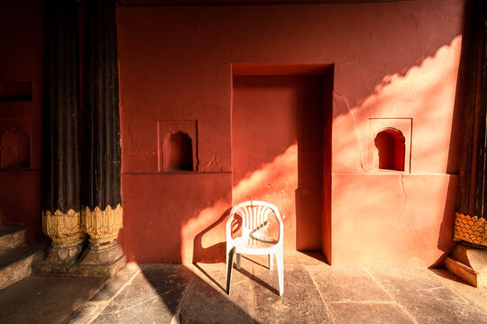 A white chair with light falling on a red wall with arched niches and teak wood pillars of the ancient Tipu Sultan Summer Palace.