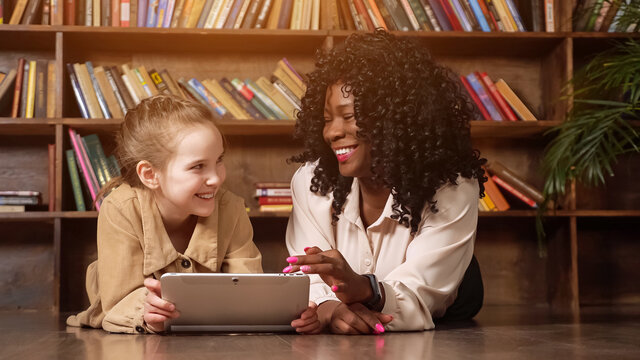 Blonde schoolgirl and Afro-American babysitter look at tablet display and laugh sitting in library with different coloured books on racks closeup, sunlight