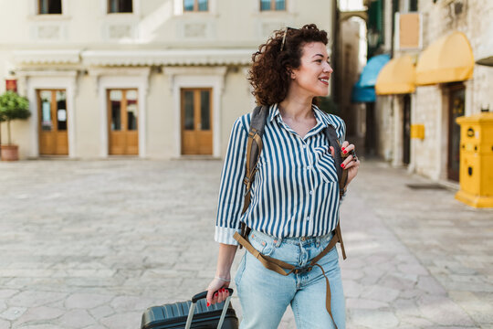 Young woman with suitcase in old city on vacation