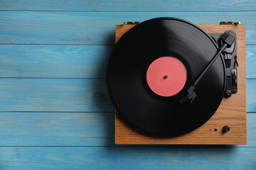 Fototapeta Modern vinyl record player with disc on blue wooden background, top view. Space for text obraz