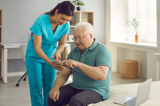 Healthcare worker, caregiver, physician or practitioner teaching chubby patient to download health app on mobile phone. Fat pensioner learning to use Internet weight loss guide for senior citizens