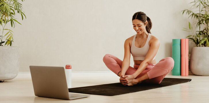 Woman exercising in fitness studio following online class