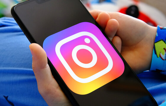 Child holing smartphone with Instagram logo. Concept for children privacy and data protection in social media. Stafford, United Kingdom, May 11, 2021.