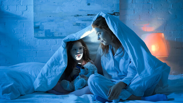 Mother and kid holding flashlight under blanket on bed in night