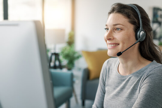 Woman wearing a headset and working with her computer