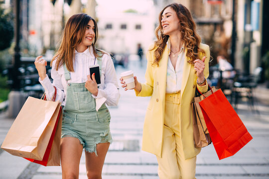 Two woman with shopping bags walking down the street