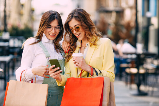 Two happy young women with shopping bags using mobile phone at the street