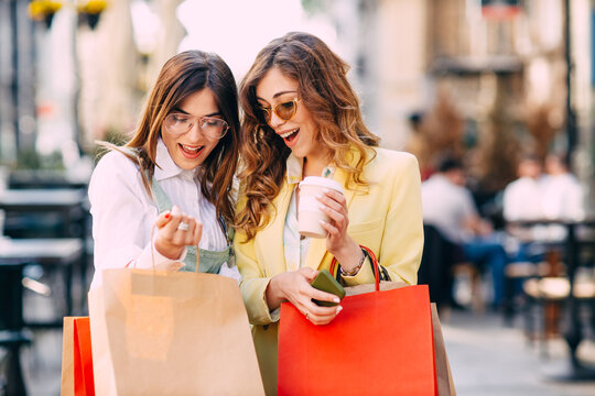 Two happy young women looking into shopping bags at the street