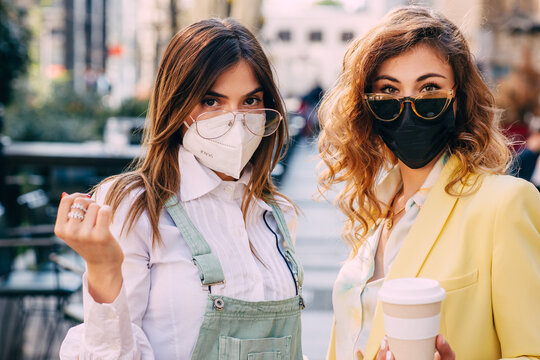 Portrait of two young female friends with protective face mask and sunglasses