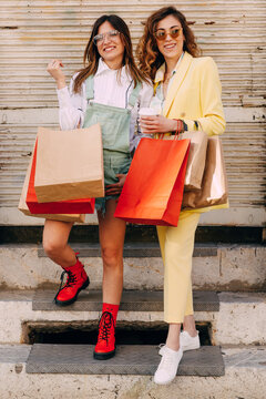 Portrait of two young female friends posing with shopping bags