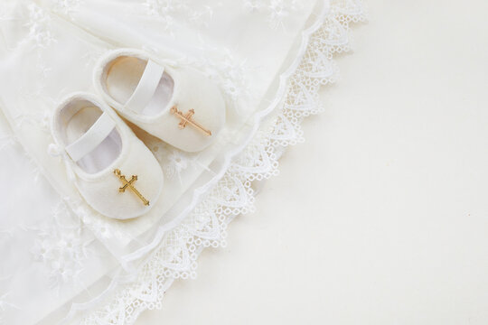 Christening background with baptism baby dress, shoes, and cross on pastel background