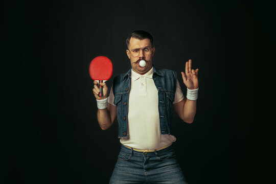 Young caucasian man playing tennis isolated on black studio background in retro style, action and motion concept
