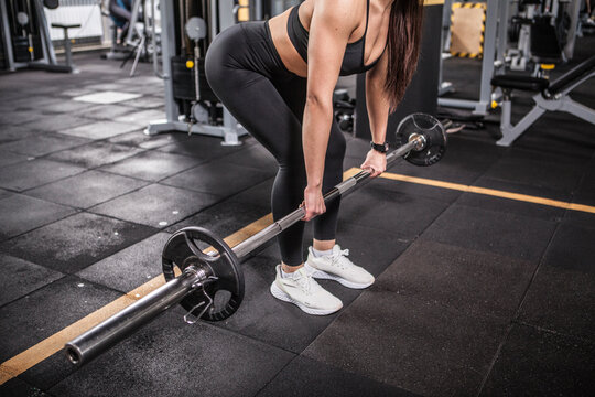 Unrecognizable woman doing deadlift exercise with barbell