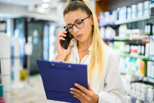Female pharmacist talking on the phone with a customer in his store