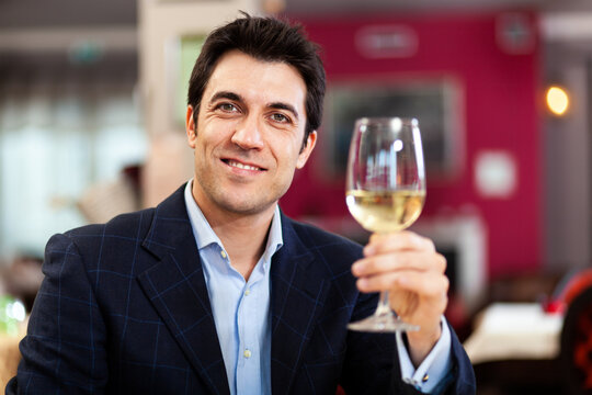 Handsome man holding a glass of white wine at the restaurant