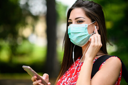 Female student walking in a park while using her smartphone to listen music and wearing a mask to protect against coronavirus covid 19 pandemic